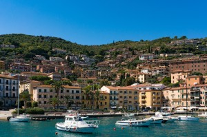 Porto Santo Stefano buildings and bay with fishing boats and yachts on a sunny summer day. Mediterranean Italian resort village of Tyrrhenian Sea with luxury property on the background